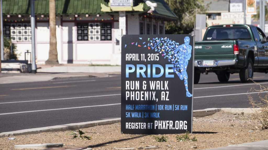 "A Queer Pride ""Run and Walk"" event is being advertised with this sign next to the roadway."